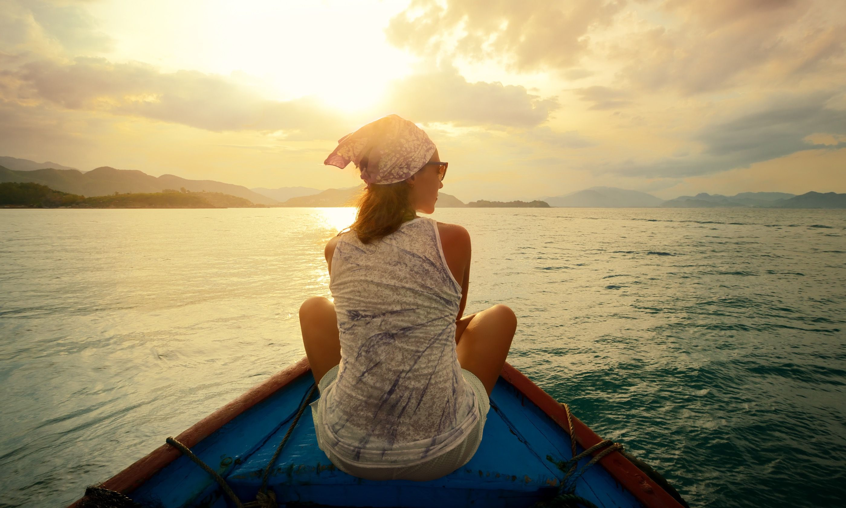 Woman contemplating sunset on a boat (Shutterstock.com)