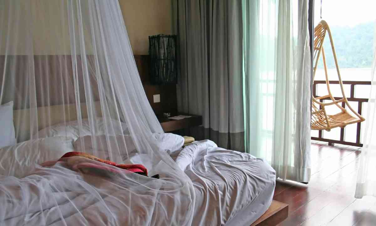 Tropical bed with mosquito net and balcony (Shutterstock)