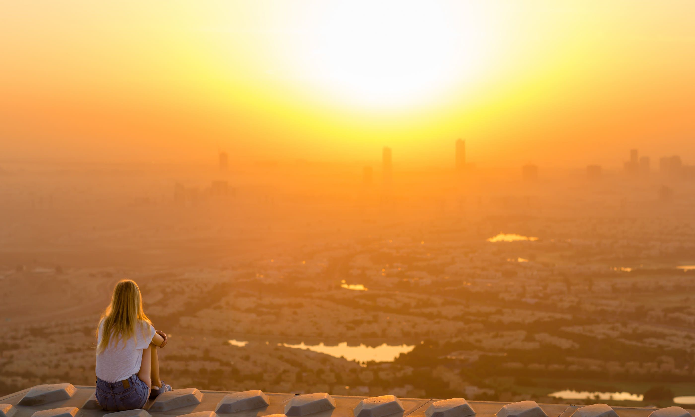Woman overlooking the city at sunrise (Shutterstock)