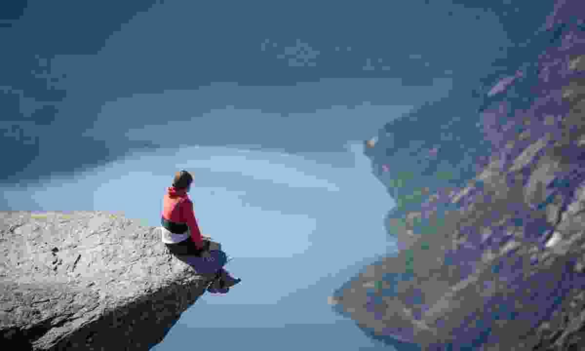 Man sitting on Trolltunga rock (Shutterstock.com)