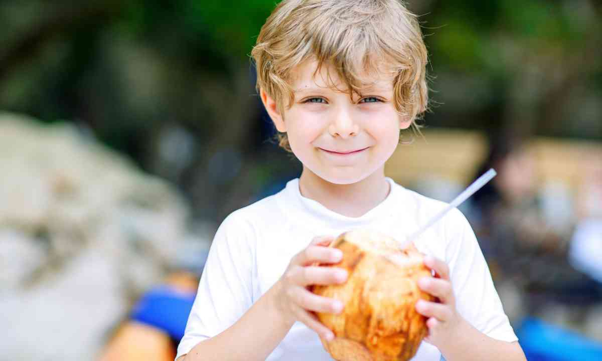 Kid drinking from coconut (Dreamstime)