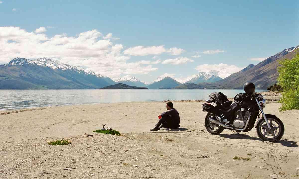 Motorcyclist resting beside a lake (Dreamstime)