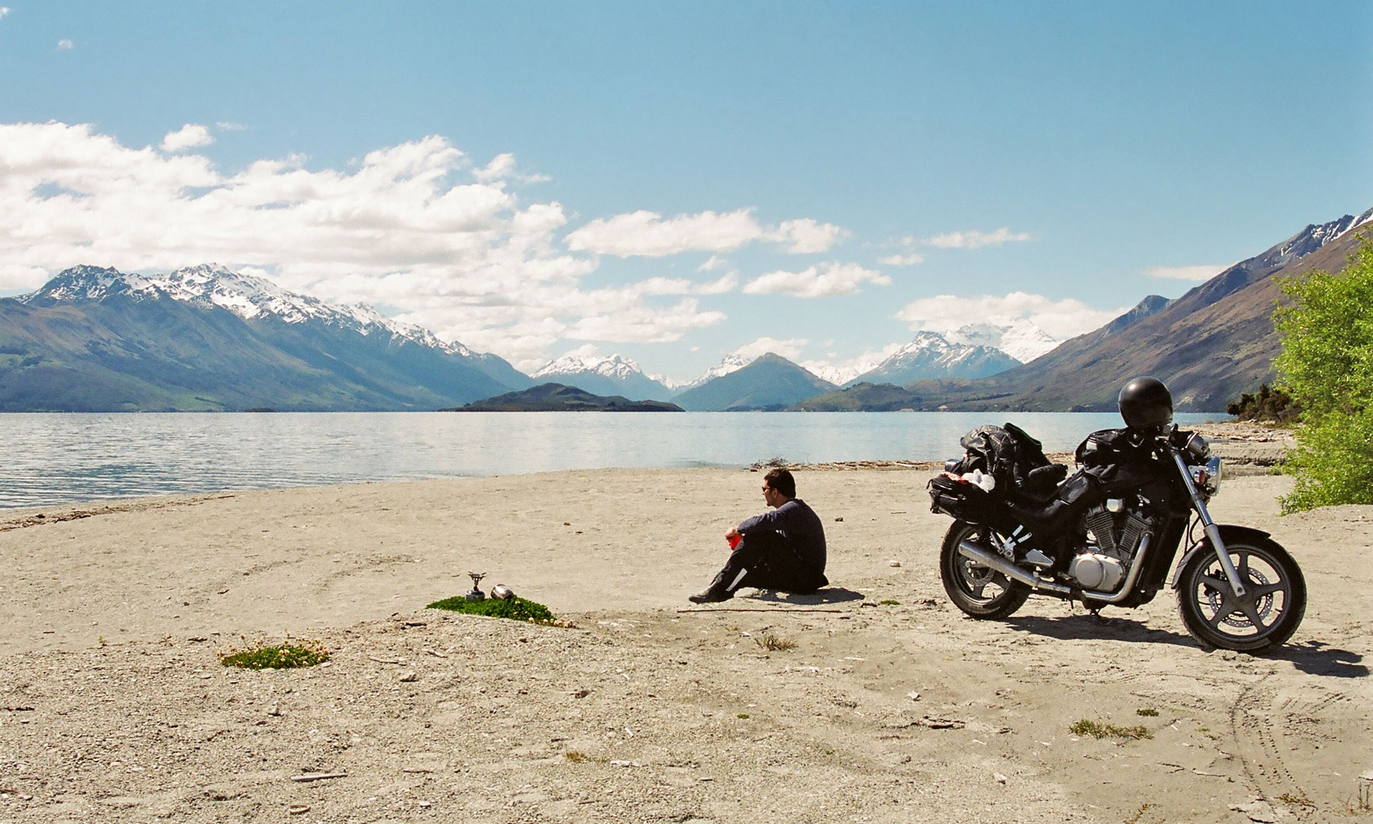 Motorcyclist resting beside a lake (Dreamstime)