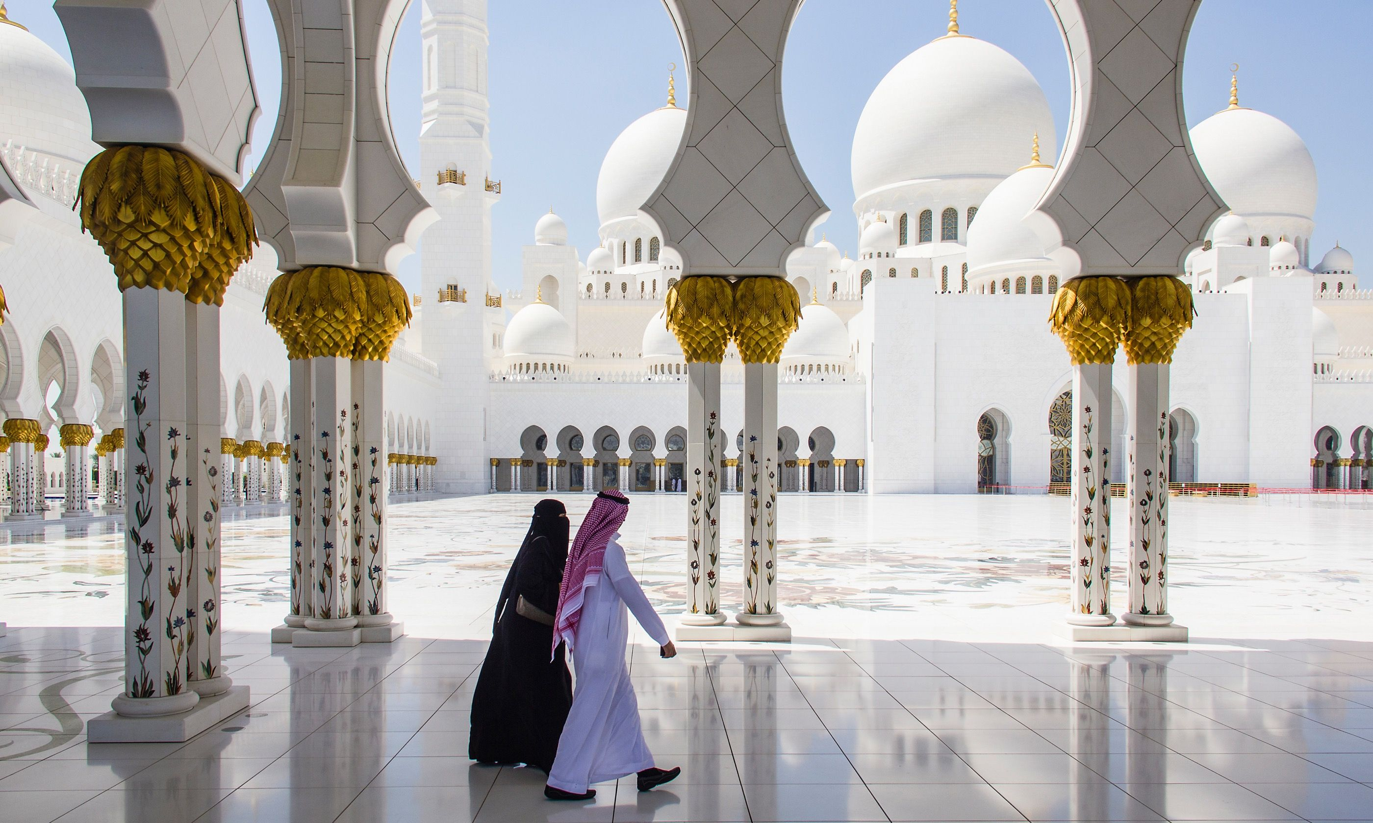 Couple walking through Sheikh Zayed Grand Mosque (Dreamstime)