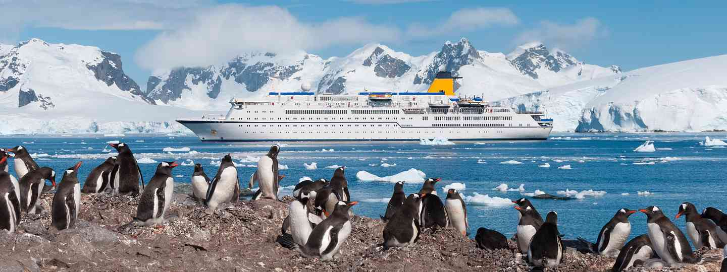 Antarctic cruise ship, watched by penguins (Dreamstime)