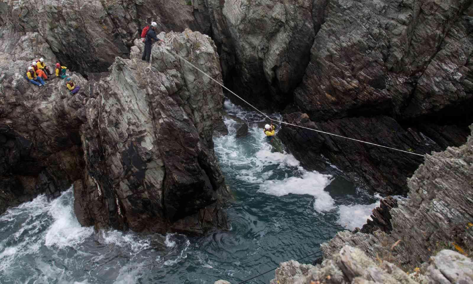 Coasteerers crossing across a gully (Shutterstock)