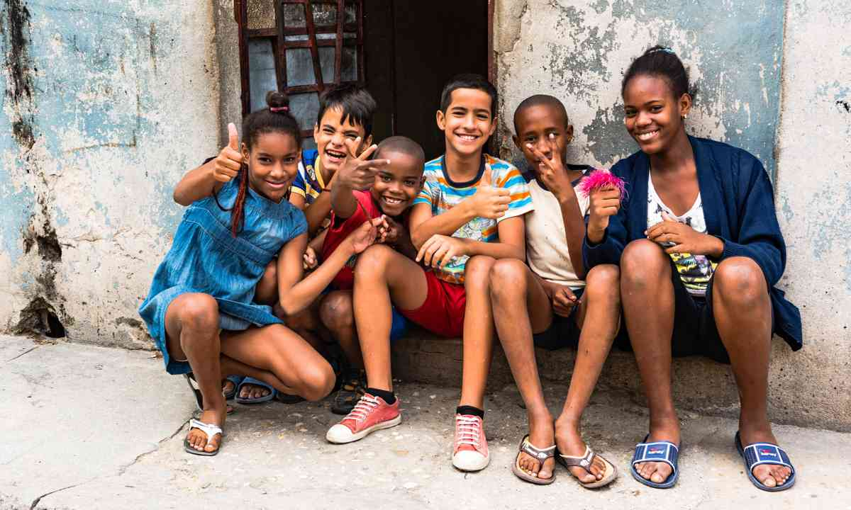 Kids sitting in front of a casas particulares in Havana (Dreamstime)