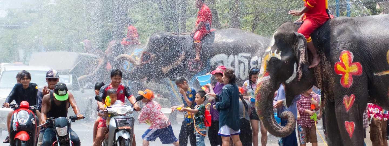 Revelers and elephants join in water splashing during Songkran Festival (Shutterstock: see credit below)