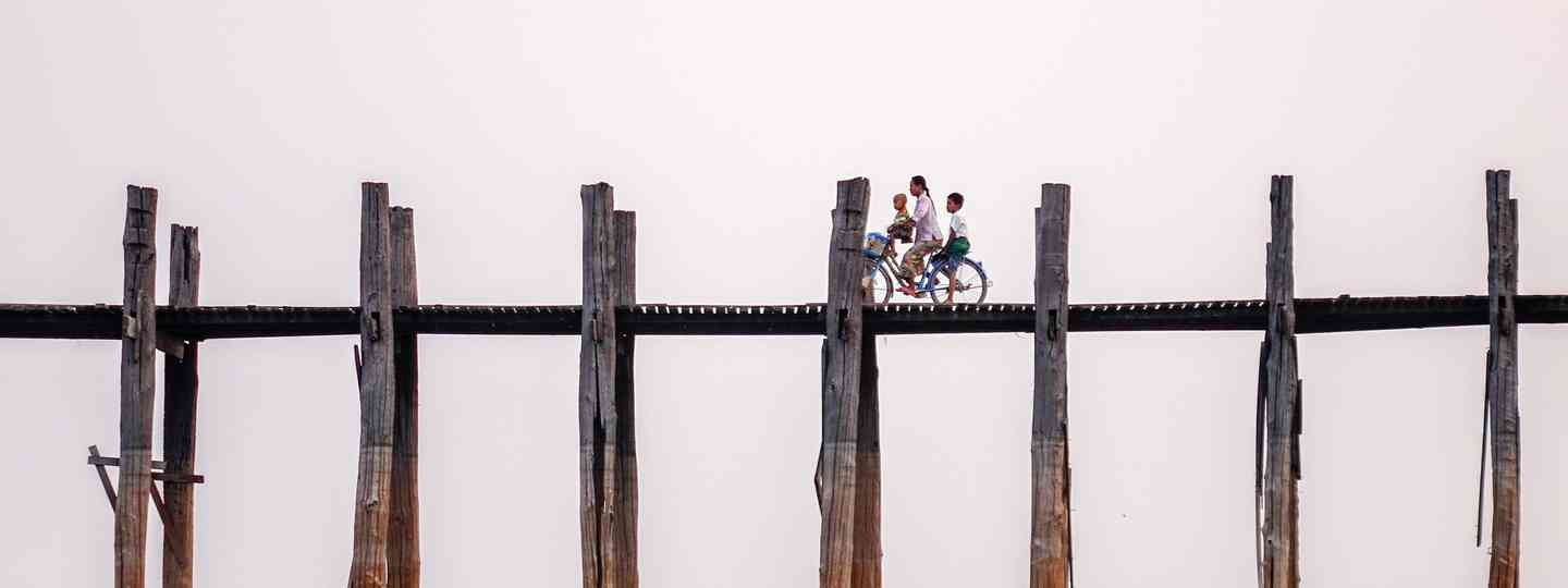 Family cycling across U Bein bridge in Burma (Dreamstime)