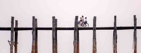 Family cycling across U Bein bridge in Burma (Dreamstime)