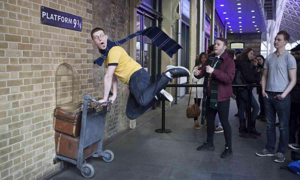 Harry Potter fans posing at Platform 9¾ (Dreamstime)