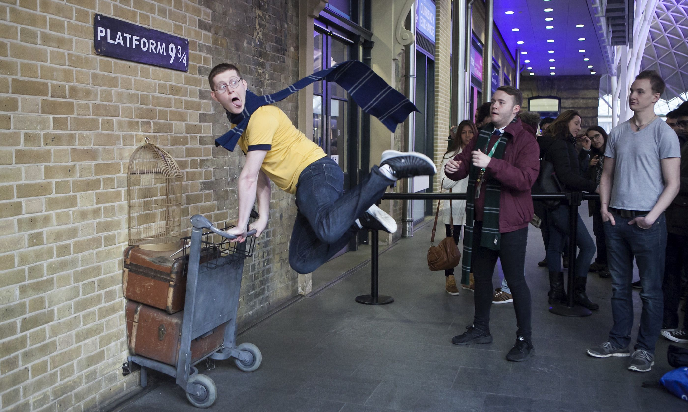Harry Potter fans posing at Platform 9¾ (Dreamstime)