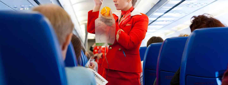 Flight attendant with passengers (Shutterstock: see credit below)