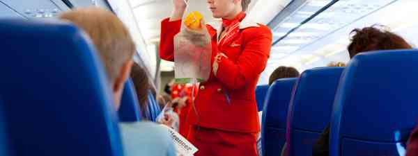 Flight attendant with passengers (Shutterstock: see credit below)
