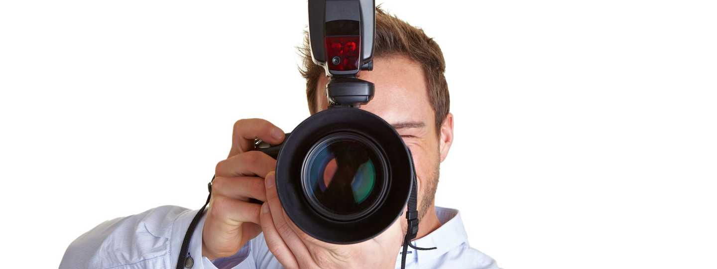 Photographer with DSLR camera and flash (Dreamstime)