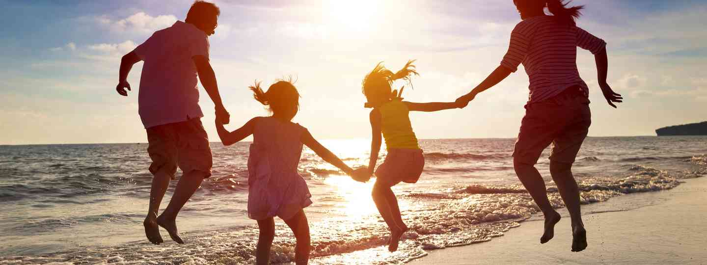 Family jumping on beach (Dreamstime)