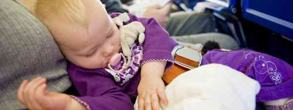 Sleeping baby on board flight. But for how long? (Dreamstime)
