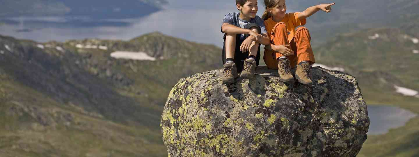 Kids sitting on a rock (Dreamstime)