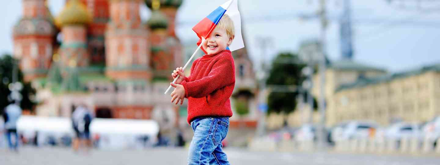 Toddler waving Russian flag in Red Square (Dreamstime)