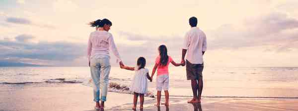 Family on beach at sunset (Dreamstime)