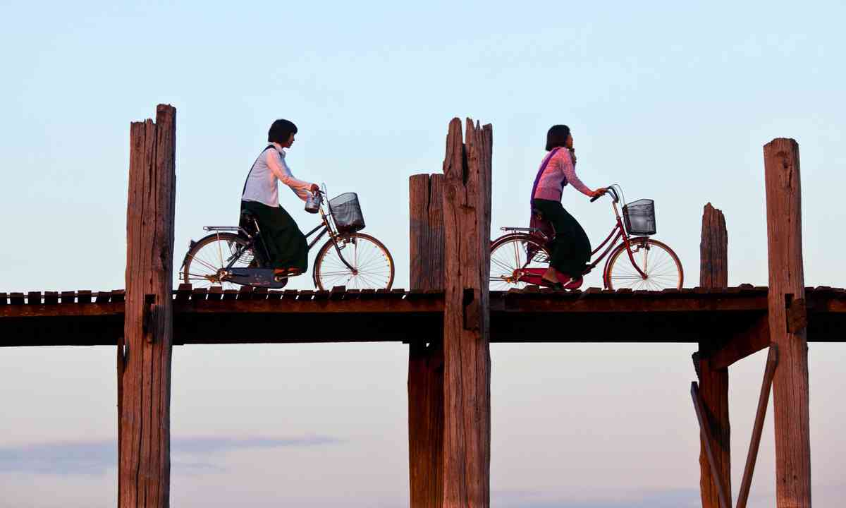 Cyclists on the U Been teak bridge (Dreamstime)
