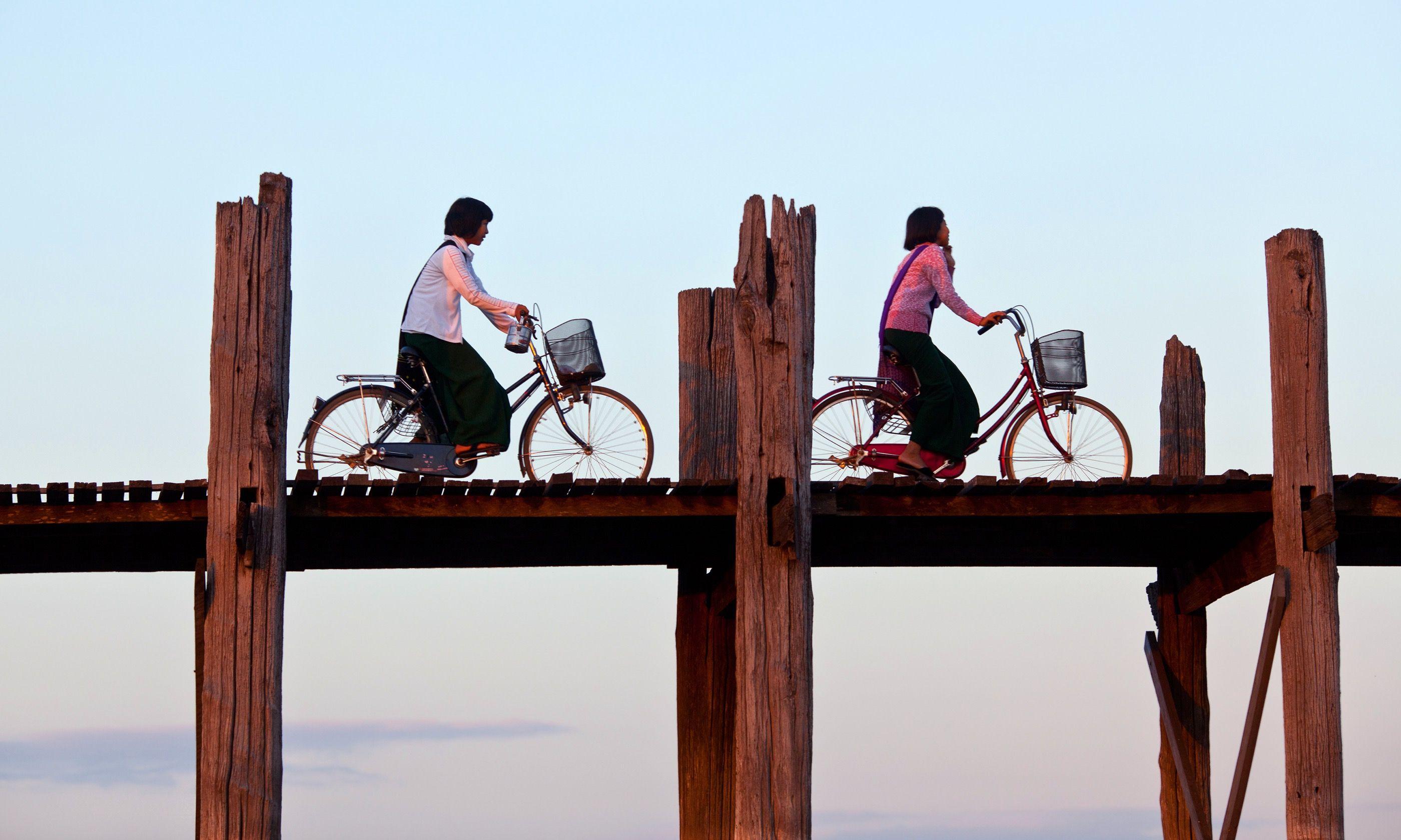 Cyclists on the U Been teak bridge (Dreamstime)