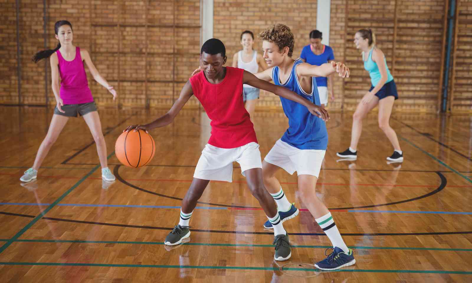 Teenagers playing basketball (Dreamstime)
