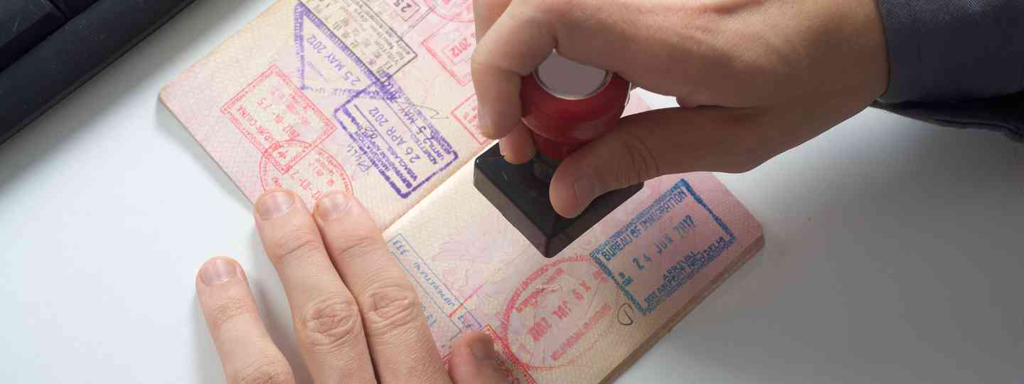 Passport being stamped by an immigration officer (Dreamstime)