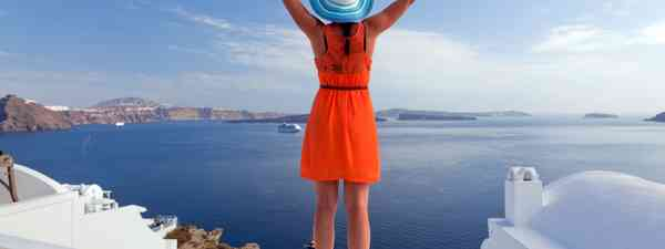 Woman embracing the view on Santorini (Dreamstime)