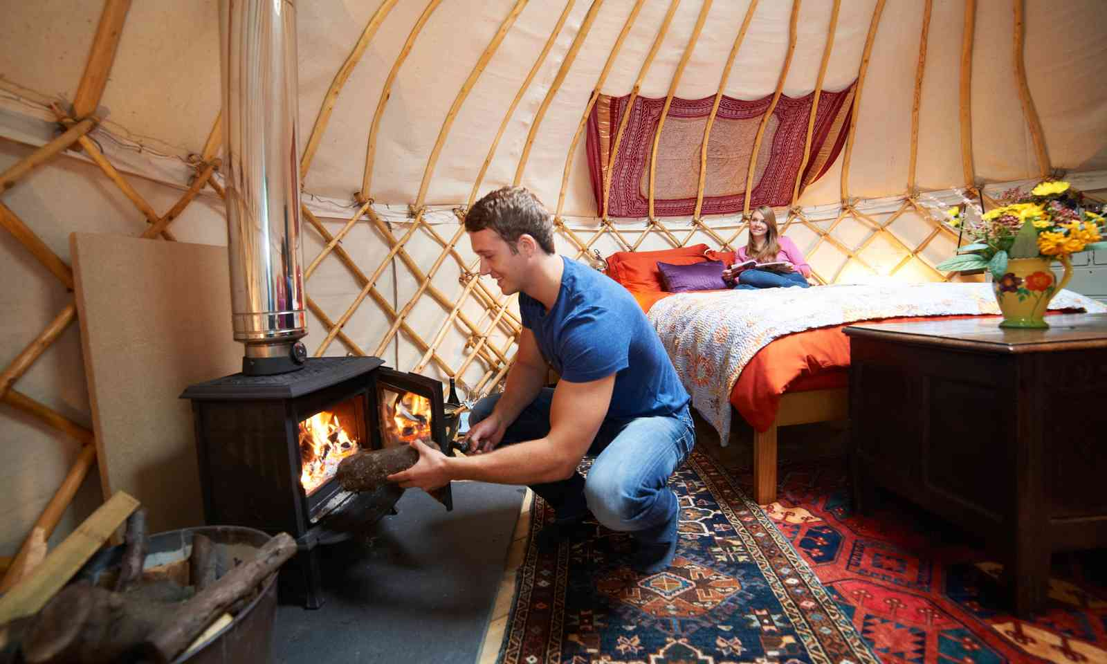 Firing up the log burner in a yurt (Dreamstime)