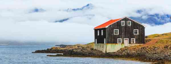 Black Wooden House at coastline in East Iceland (Shutterstock)
