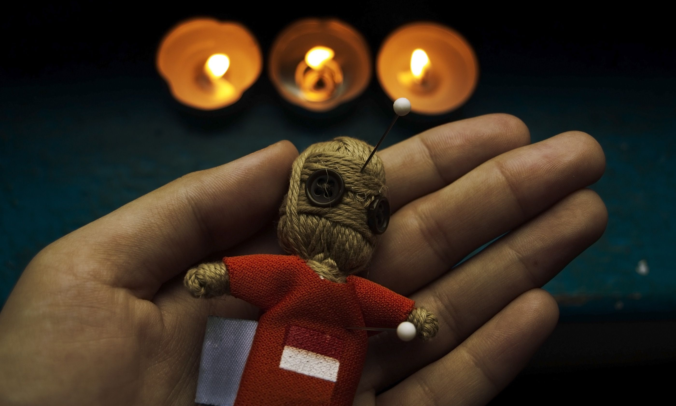 Voodoo doll with candles (Shutterstock.com)