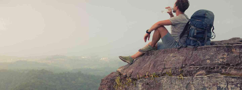 Hiker drinking a bottle of water on mountain top (Shutterstock)