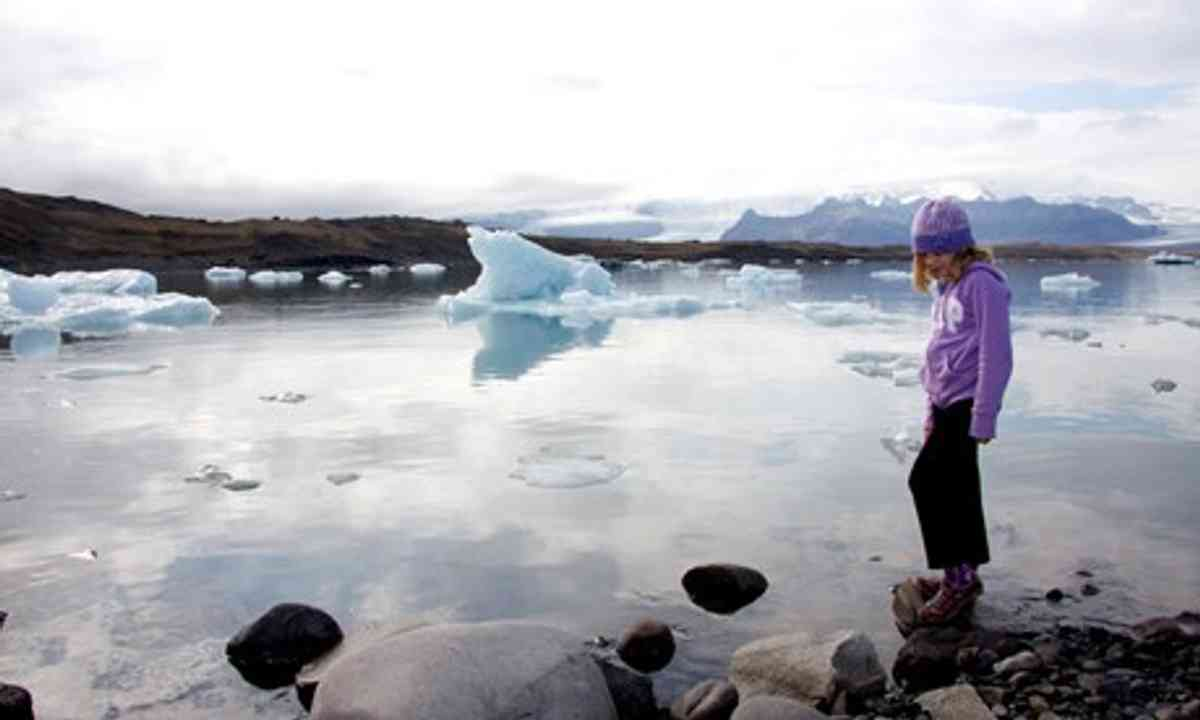 Child contemplating glacier lake, Iceland (Peter Moore)