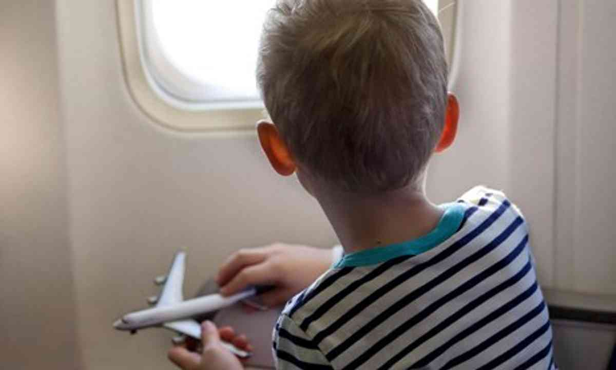 Boy on plane playing with toy plane (Shutterstock.com)