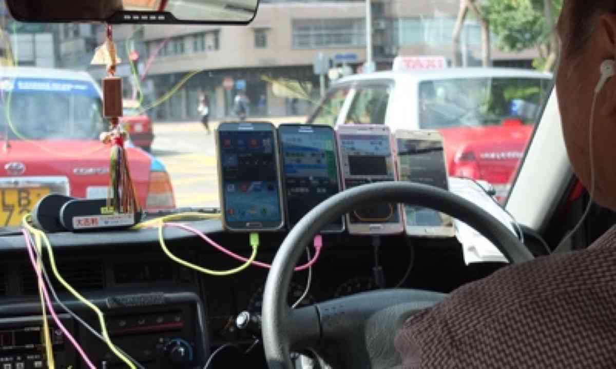 Multitasking taxi driver, Hong Kong (Matthew Woodward)