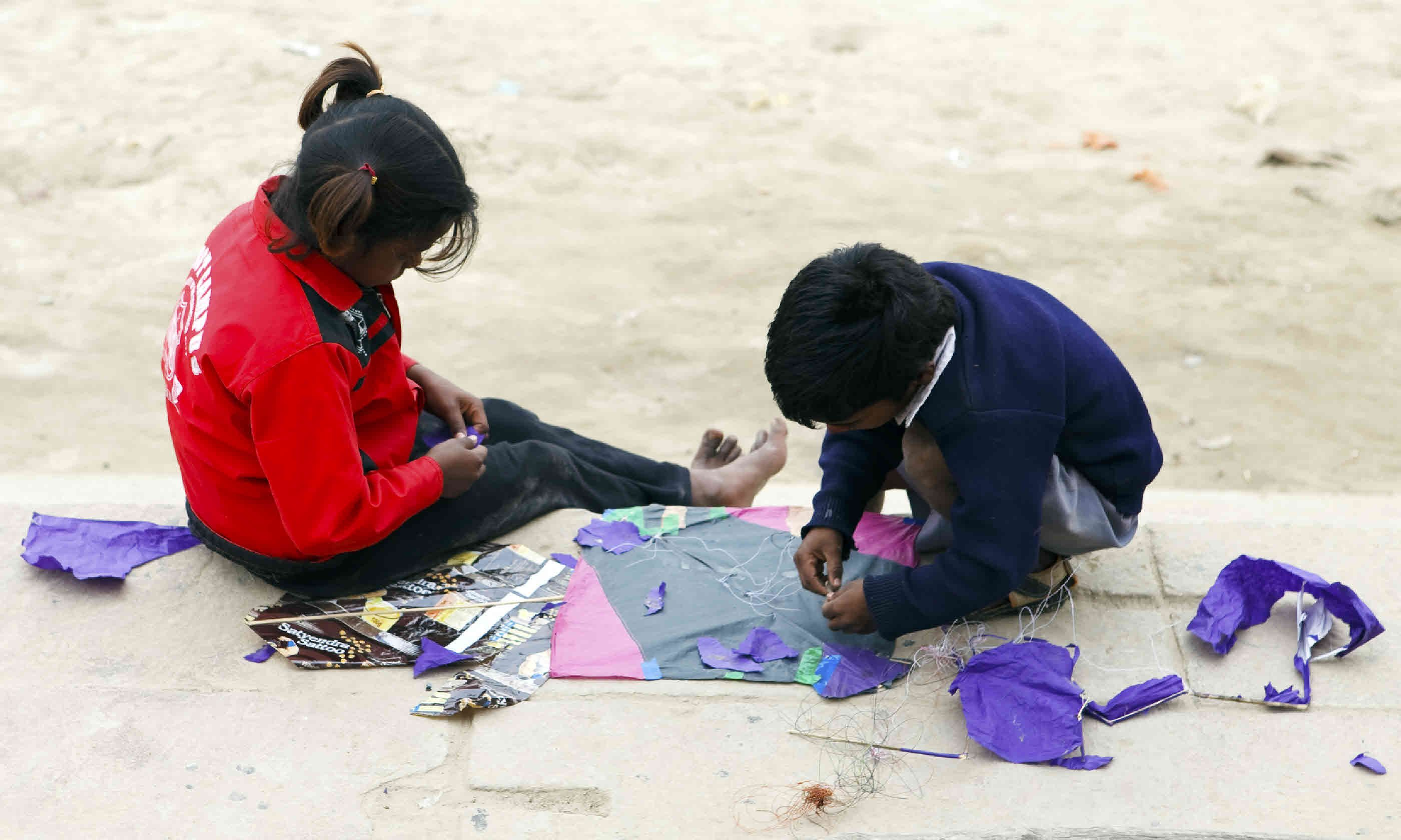 Children repair a kite on the banks of the Ganges (Shutterstock)