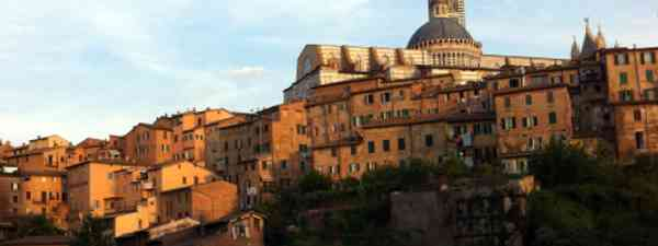 Siena at sunset is bathed in a warming orange glow (Daisy Cropper)