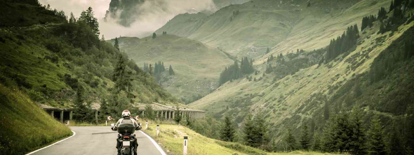 Motorcyclist on mountainous highway (Shutterstock: see credit below)